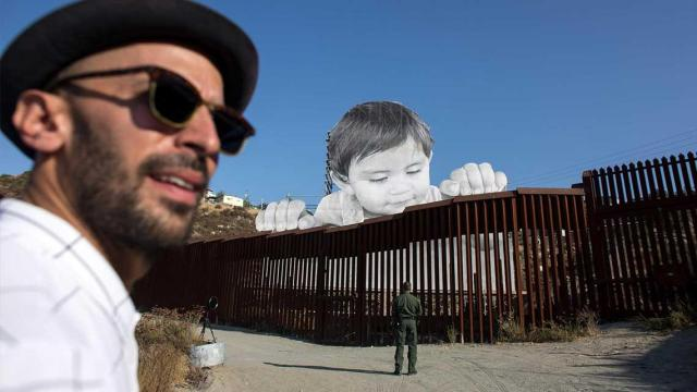 Anonymous-Artist-Adds-A-Giant-Baby-To-The-USMexico-Border-Wall